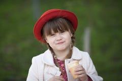 Fille drôle avec des tresses dans le chapeau mangeant la crème glacée  Photo stock
