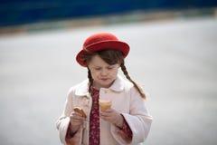 Fille drôle avec des tresses dans le chapeau mangeant la crème glacée  Images libres de droits
