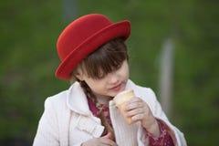 Fille drôle avec des tresses dans le chapeau mangeant la crème glacée  Image stock