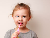 Fille drôle d'enfant brossant les dents Photo stock