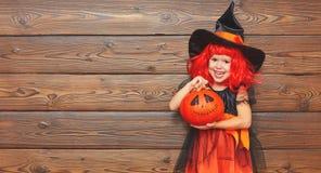 Fille drôle d'enfant dans le costume de sorcière pour Halloween avec le potiron Ja Photos stock