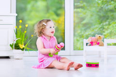 Fille drôle d'enfant en bas âge jouant des maracas dans la chambre blanche Image stock