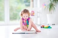 Fille drôle d'enfant en bas âge lisant un livre se reposant sur un fllor photo libre de droits