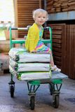 Fille drôle d'élève du cours préparatoire s'asseyant sur le chariot à achats Photo stock