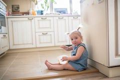 Fille drôle de petit enfant en bas âge caucasien avec des tresses mangeant le cre de glace Image stock
