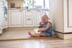 Fille drôle de petit enfant en bas âge caucasien avec des tresses mangeant le cre de glace Photos libres de droits