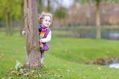Fille drôle douce d'enfant en bas âge se cachant derrière l'arbre dans le parc photo stock