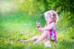 Fille drôle mignonne mangeant la crème glacée dans le jardin ensoleillé Photos stock