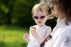Fille drôle d'enfant en bas âge mangeant le biscuit Images libres de droits
