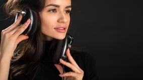 Fille du DJ dans des battements de écoute de disco d'écouteurs posant dans le studio au-dessus du fond foncé Jeune modèle caucasi photos stock