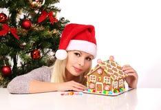 Fille effectuant la maison de pain d'épice Jeune femme avec le chapeau de Santa Photo stock