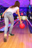 Fille effectuant le jet de la bille dans le club de bowling Photos libres de droits