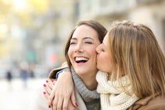 Fille embrassant à son ami heureux en hiver Image stock