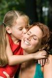 Fille embrassant la mère Photographie stock