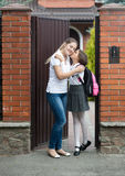 Fille embrassant la mère avant de partir pour l'école Images stock