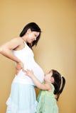 Fille embrassant la mère enceinte Images libres de droits