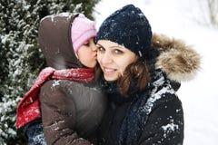 Fille embrassant la mère parmi la neige Images stock