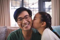 Fille embrassant le père sur des joues dans le salon Image stock