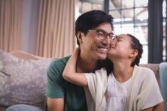 Fille embrassant le père sur des joues dans le salon Photo stock