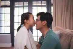 Fille embrassant le père sur le nez dans le salon Image stock