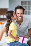 Fille embrassant le père tenant le boîte-cadeau Photos libres de droits
