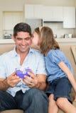 Fille embrassant le père tenant le boîte-cadeau sur le sofa Photo stock