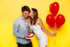 Fille embrassant son ami après l'obtention d'un présent le jour du ` s de Valentine Photographie stock
