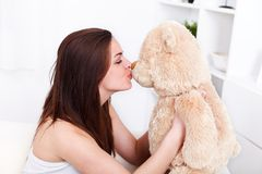 Fille embrassant son ours de nounours Photos stock