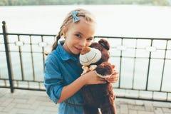 Fille embrassant un ours de nounours mignon Photos stock