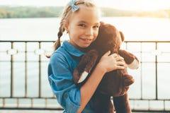 Fille embrassant un ours de nounours mignon Photographie stock libre de droits