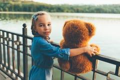 Fille embrassant un ours de nounours mignon Photographie stock