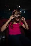 Fille employant les verres 3D tout en observant le film Image libre de droits