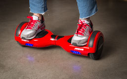 Fille employant un rouge auto-équilibrant le conseil à deux roues Le gyroscope a basé la double roue s électrique Images libres de droits
