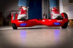 Fille employant un rouge auto-équilibrant le conseil à deux roues Le gyroscope a basé la double roue s électrique Photos stock