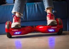Fille employant un rouge auto-équilibrant le conseil à deux roues Le gyroscope a basé la double roue s électrique Image libre de droits