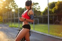 Fille en bonne santé de forme physique avec le téléphone intelligent Photos stock