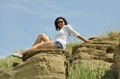 Fille en chemisier blanc et verres à côté de la roche Image libre de droits