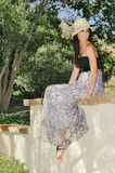 Fille en Maxi Dress Sitting sur le mur Images stock