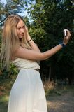 Fille en parc avec votre smartphone Images stock