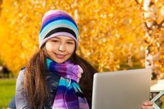 Fille en parc d'automne avec le comprimé Photographie stock libre de droits