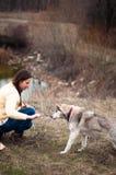 Fille en parc leur maison avec un chien de traîneau de chien La fille avec Image libre de droits