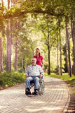 Fille en parc poussant appréciant l'homme supérieur dans le fauteuil roulant Photographie stock libre de droits