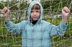 Fille en parc tenant la grille photographie stock libre de droits