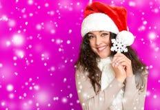 Fille en portrait de chapeau de Santa avec le grand jouet de flocon de neige posant sur le fond de couleur, le concept de vacance Photographie stock