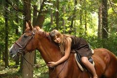 Fille en robe et portrait brun de cheval dans la forêt Photographie stock libre de droits