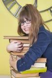 Fille en verres étreignant une pile de livres Photographie stock