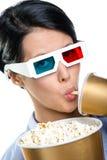 Fille en verres 3D avec la boisson et le bol de maïs éclaté Photographie stock libre de droits