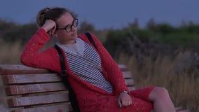 Fille en verres se reposant sur le banc observant la mer de soirée banque de vidéos