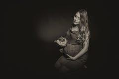 Fille enceinte avec des fleurs Photographie stock libre de droits