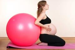 Fille enceinte avec une boule pour la forme physique image stock